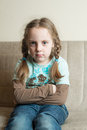 Little angry girl sitting on a couch at home being looking at the camera Stock Images