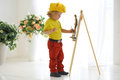 A little artist in the yellow cap paints on an easel Stock Photos
