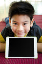 Little asian boy smiles with tablet computer acting on his face Royalty Free Stock Photos