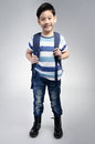 Little asian child standing with a kit bag slung over his should shoulder on gray background Stock Image