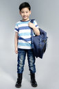 Little asian child standing with a kit bag slung over his should shoulder on gray background Stock Photography