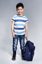 Little asian child standing with a kit bag slung r on gray background Royalty Free Stock Image