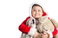 Little Asian fat boy in santa costume hugging rabbit doll on chr Royalty Free Stock Photo
