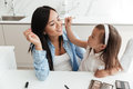 Little asian girl applying make up on her mothers face Royalty Free Stock Photo