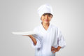 Little asian girl chef showing the empty white plate isolated on grey Royalty Free Stock Photos