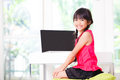 Little asian girl with computer at home Stock Image