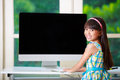 Little asian girl with computer at home Stock Images