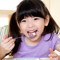 Little asian girl eating with spoon Royalty Free Stock Photo