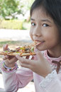 Little Asian girl enjoy pizza. Royalty Free Stock Photo