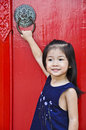 Little asian girl in front of ancient red door. Stock Image