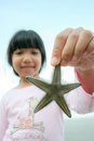 Little Asian girl holding starfish Royalty Free Stock Photo