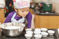 Little asian girl making cotton wool cake mixing flour to in kitchen Stock Photography