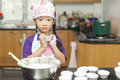 Little asian girl making cotton wool cake mixing flour to in kitchen Royalty Free Stock Image