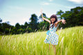 Little asian girl with open arms against green meadow outdoor portrait Stock Images