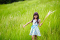 Little asian girl with open arms against green meadow outdoor portrait Royalty Free Stock Photos