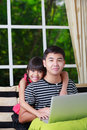 Little asian girl pointing on laptop with big brother at home Royalty Free Stock Photo