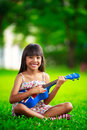 Little asian girl sitting on grass and play ukulele outdoor portrait Stock Photo