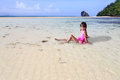 Little asian girl sitting at tropical beach outdoor portrait Stock Photos