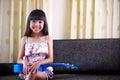 Little asian girl sitting with ukulele smiling Royalty Free Stock Image