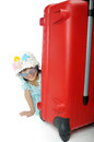 Little asian girl in a weave hat and sunglasses sitting behind h huge travel red suitcase Stock Photo
