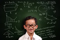 Little asian student boy math genius with glasses smiling over green chalkboard with equivalents written on it Royalty Free Stock Image