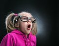 Little astonished girl in funny big spectacles on grey background Stock Photo