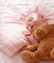 Little baby asleep with plush bear toy newborn girl napping in the bed at home child care closed eyes healthy lifestyle happy Royalty Free Stock Photos