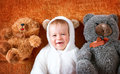 Little baby in bear costume with plush toys