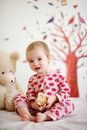 Little baby in bed wearing red pyjamas Royalty Free Stock Images