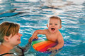 Little baby with blue eyes learning to swim mother focus on Stock Photo