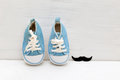 Little baby blue sneakers for boy and mustaches on a white woode Royalty Free Stock Photo