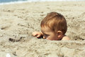 Little baby boy hiding in sand on the beach Royalty Free Stock Image