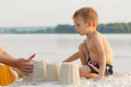 Little baby boy is resting on the sandy shore, build a castle Royalty Free Stock Photo