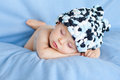 Little baby boy sleeping with hat on a blue background Royalty Free Stock Photography