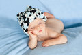 Little baby boy sleeping with hat on a blue background Stock Image