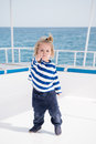 Little baby captain on boat on summer cruise, nautical fashion Royalty Free Stock Photo