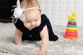 Little baby in dress creeps on grey soft carpet with colorful toy pyramid Royalty Free Stock Photos