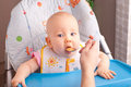 Little baby feeding with a spoon at the kitchen Stock Photo