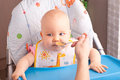 Little baby feeding with a spoon at the kitchen Stock Images