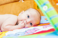 Little baby with finger in mouth on the playing mat Royalty Free Stock Photography