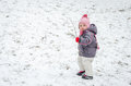Little baby girl beautiful winter day playing in the snow wearing a jacket hooded down jacket, trousers, hat and gloves Royalty Free Stock Photo