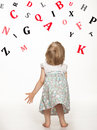 Little baby girl catching something letters of alphabet Stock Photos