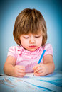 Little baby girl draws pencil blue background Royalty Free Stock Images