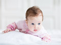 Little baby girl enjoying tummy time in a pink cardigan Royalty Free Stock Photo