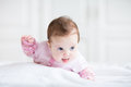 Little baby girl enjoying tummy time in a pink cardigan Royalty Free Stock Images