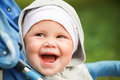 Little baby girl laughs in pram on the walk Stock Images