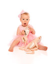 Little baby girl in a pink ballerina dress with pointe shoes isolated on white background Stock Photo