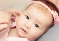 Little baby girl with pink flower headband exploring the world w cute while mother dressing her Stock Image