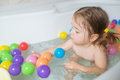 Little baby girl playing with colored balls Royalty Free Stock Photo