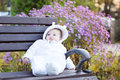 Little baby girl sitting on a bench next to a violet flower bush Royalty Free Stock Photo